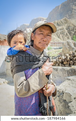 Residents Kee famous village where the monastery Kee Gompa. Father and small son on his shoulders at the father go for ...