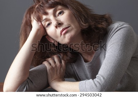 resigned mature woman resting her face on her hands thinking about her aging problems or senior depression - stock photo