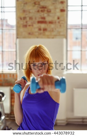 Resolute shapely young woman working out with dumbbells in a gym extending her hand towards the camera, focus to her face and look of determination - stock photo