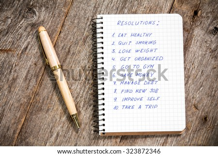 Resolutions listed in the notepad on the wooden background - stock photo