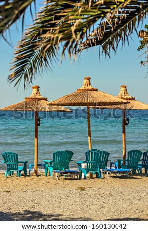 Resort beach with chairs and straw parasol
