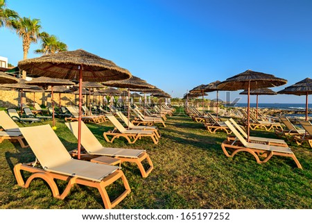 Resort beach with chairs and straw parasol - stock photo