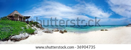 resort bungalow on tropical beach with turquoise waters panorama - stock photo