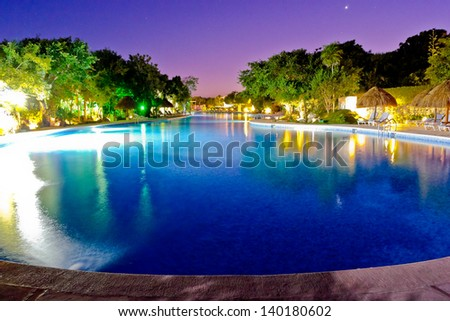 Resort  swimming pool at night time - stock photo