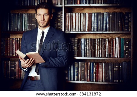 Respectable young man in the old library. Classic vintage interior. - stock photo