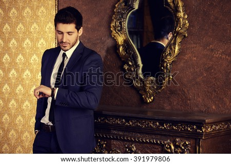 Respectable young man standing by a fireplace in a room with classic interior. Luxury. Men's beauty, fashion. - stock photo