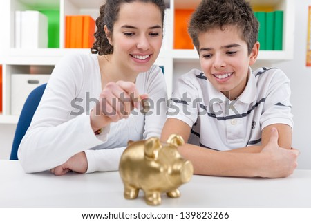 Responsible brother and  sister putting money into piggy bank for future saving - stock photo