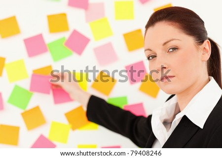 Responsible woman putting re-positionable notes on a white wall
