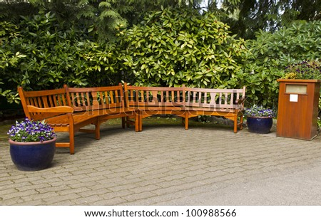 Rest area with joining cedar benches on brick pathway with trees in background - stock photo
