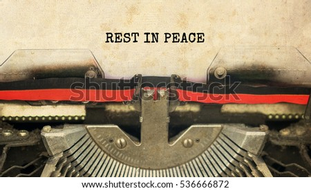 REST IN PEACE typed words on a vintage typewriter with vintage background