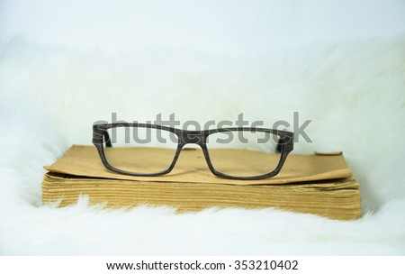 rest your eyes and put glasses. glasses on old book on white soft fabric background - stock photo