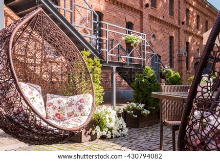 Restaurant and cafe with comfortable wicker hanging swing outdoor - stock photo