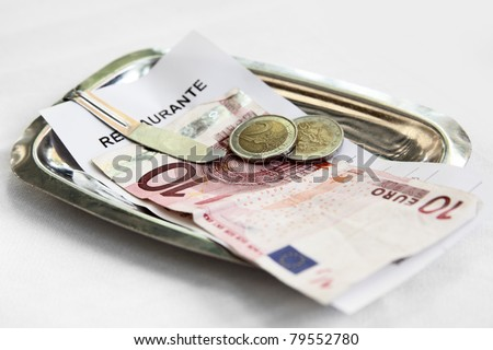 Restaurant bill and money on matal tray
