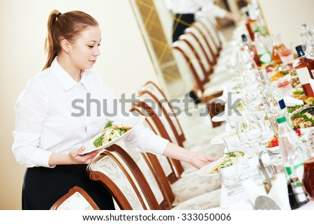 Restaurant catering services. Waitress with salad dish serving banquet table - stock photo