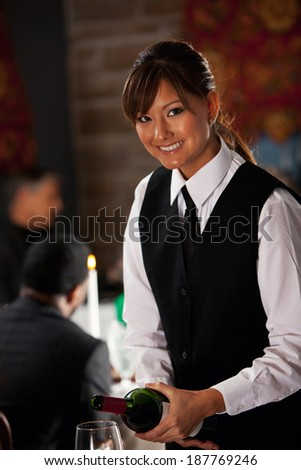 Restaurant: Cheerful Sommelier Pouring Wine - stock photo