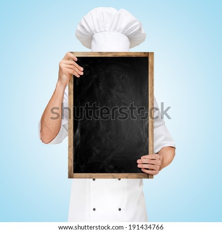 Restaurant chef hiding behind a blank chalkboard for a business lunch menu with prices. - stock photo