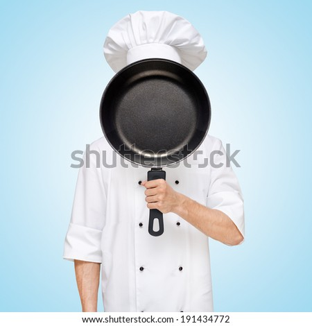Restaurant chef hiding behind a frying pan for a business lunch menu with prices. - stock photo