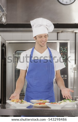 Restaurant chef standing proudly presenting prepared gourmet meals in an industrial kitchen setting