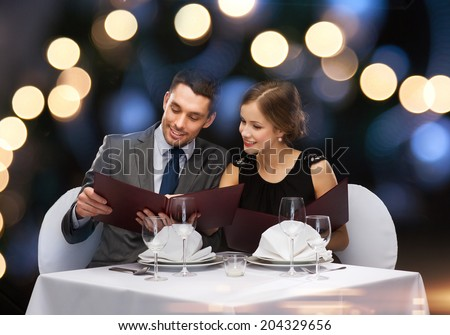 restaurant, couple and holiday concept - smiling couple with menus at restaurant - stock photo