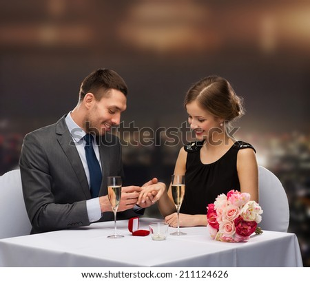 restaurant, couple and holiday concept - smiling man putting on finger engagement ring at restaurant - stock photo