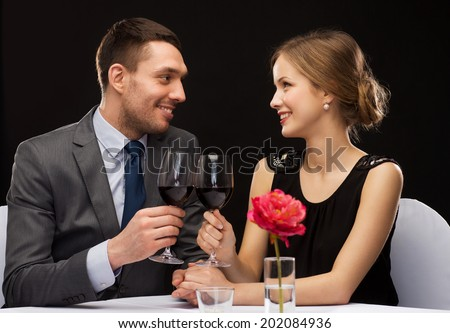 restaurant, couple and holiday concept - smiling young couple with glasses of red wine looking at each other at restaurant - stock photo