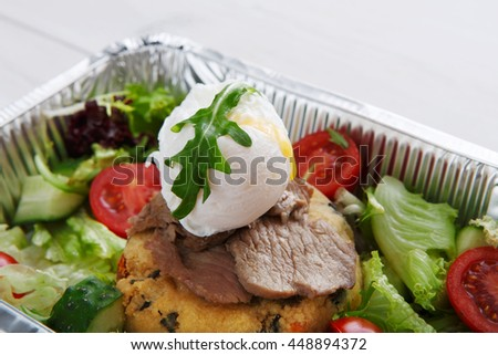 Restaurant food delivery in foil box. Poached egg closeup on veil steak medium rare with fresh vegetable salad and couscous cushion. Dish take away closeup, healthy meal.