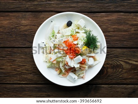 Restaurant food top view. Flat lay. Fresh mediterranean cuisine. Salad with Seafood, Feta Cheese and Vegetables, decorated with fennel. Catering, banquet wooden table. Shrimps salad served at wood.  - stock photo