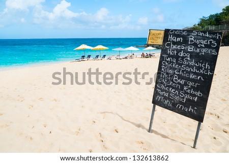 Restaurant menu on blackboard display at tropical beach - stock photo