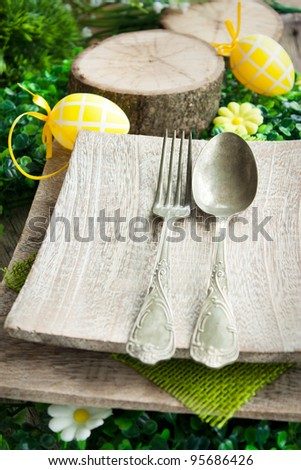 Restaurant menu series. Easter place setting. Fork and knife in rustic country table setting - stock photo