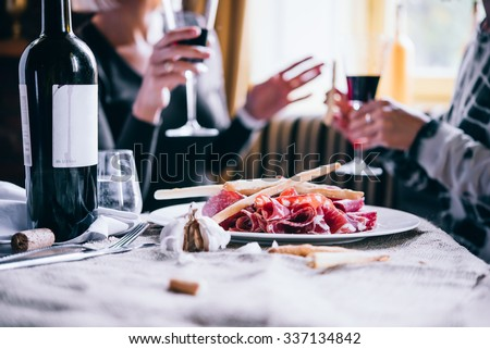 Restaurant or bar table with plate of appetizers and wine. Two people talking on background - stock photo