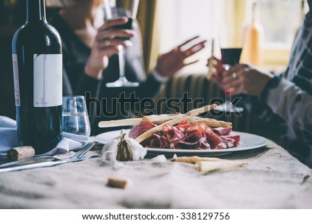 Restaurant or bar table with plate of appetizers and wine. Two people talking on background. Toned picture - stock photo