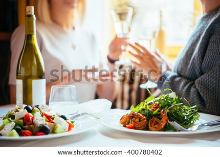 Restaurant or cafe table with plate of salads and wine. Two people talking on background - stock photo