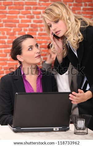 Restaurant owner using a laptop and taking a call - stock photo