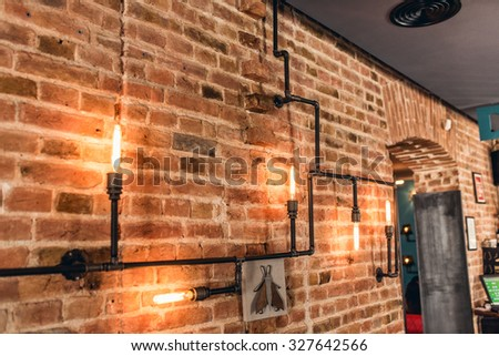 restaurant rustic walls, vintage interior design lamps, metal pipes and light bulbs - stock photo