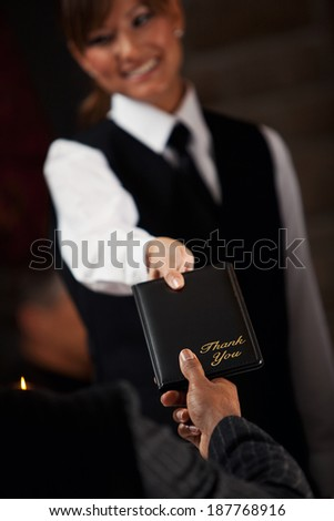 Restaurant: Server Delivers Bill To Table - stock photo