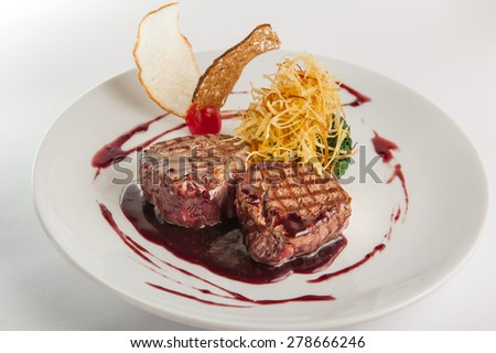 Restaurant serves meat steak with spinach pillow and potato's brushwood in berry sauce, garnished with breadcrumbs and cherry tomatoes on white plate isolated
