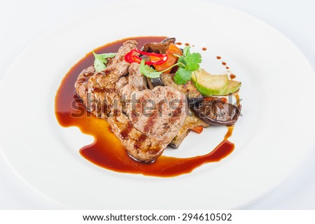 Restaurant serves meat steak with stewed vegetables and sauce: zucchini, eggplant, carrots, mushrooms, decorated with herbs and spices on white plate isolated - stock photo