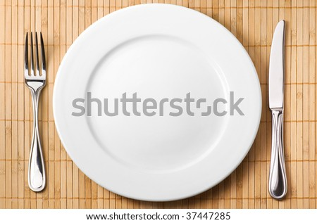 Restaurant serving (metal fork, knife and ceramic white plate) - stock photo