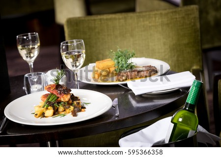 Restaurant table set up for two main dish steak fish cuisine fries fine dinning white wine & Restaurant Table Set Two Main Dish Stock Photo (Safe to Use ...
