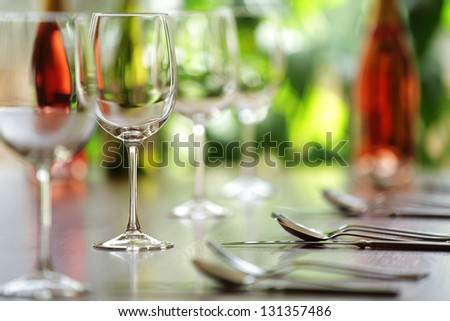 Restaurant table with cutlery, wine and wine glasses ready for a dinner party - stock photo