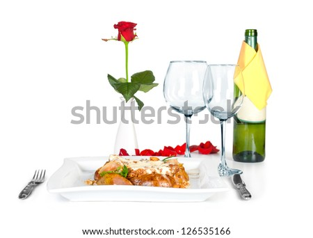 restaurant table with meat with vegetables and glass for wine and bottle