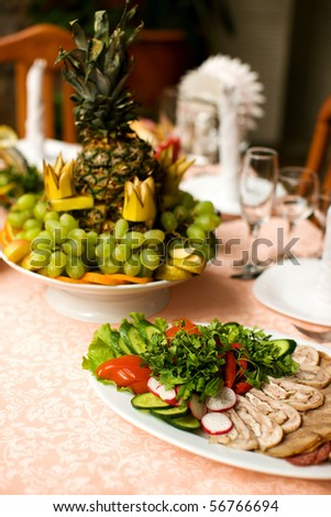 Restaurant table with snack and fruits on it - stock photo