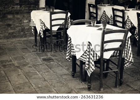 Restaurant tables at the street. Old photo effect applied. - stock photo