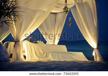 Restaurant tent with table served on the beach - stock photo