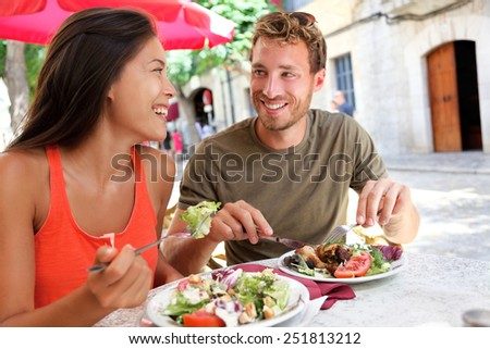 Restaurant tourists couple eating at outdoor cafe. Summer travel people eating healthy food together at lunch during holidays in Mallorca, Spain. Asian Caucasian multiracial young adults.