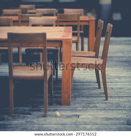 Restaurant wooden table and chairs with selective focus with vintage looks. - stock photo