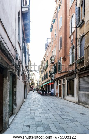 "restaurants and people eating in the street called ""dei Boteri"" in Venice, Italy"