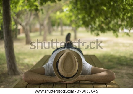 Restful young man wearing a straw hat laying down on a wooden table in the middle of the forest at a park - stock photo