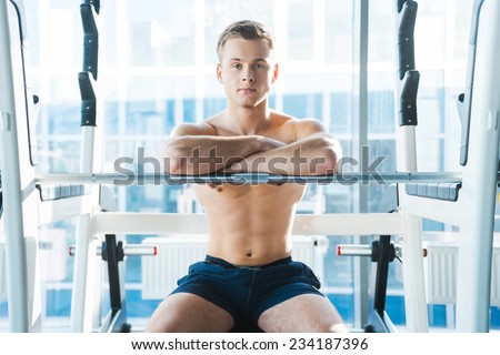 Resting after workout session. Confident young muscular man keeping arms crossed and looking at camera while sitting at the bench press - stock photo