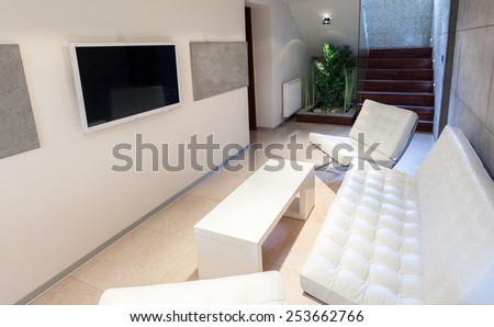 Resting area with a tv and white sofa - stock photo